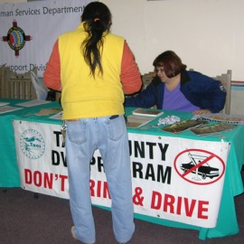 Summit attendee viewing resources at the Taos County DWI program table