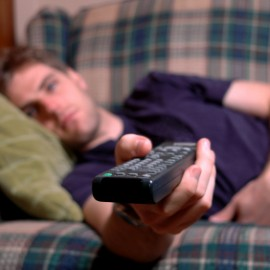 Weary looking young man lies on sofa extending a remote control.