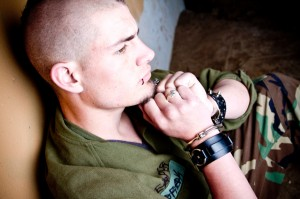Young man wearing handcuffs, sitting back againts a wall, looking angry.