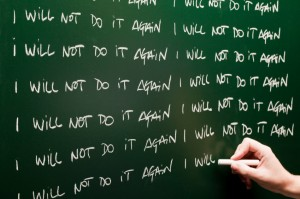"""Chalkboard with a hand writing """"I will not do it again"""" many times"""