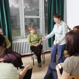 Woman standing, talking to seated women grouped in a circle, gesturing emotionally